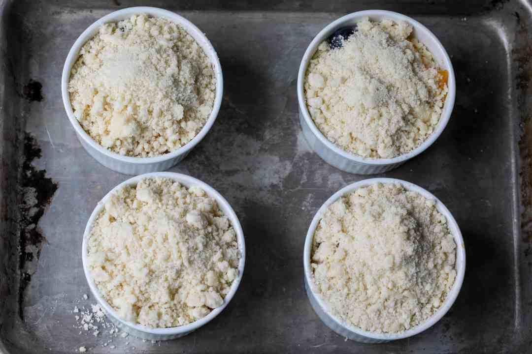 4 ramekins of peach blueberry crumble, uncooked, on sheet pan