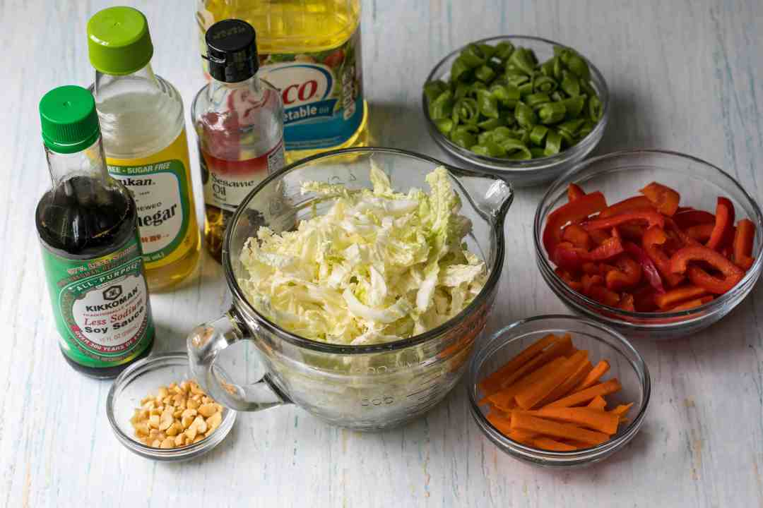 Ingredients for asian cabbage slaw in bowls next to oil, vinegar, sesame oil, and soy sauce bottles