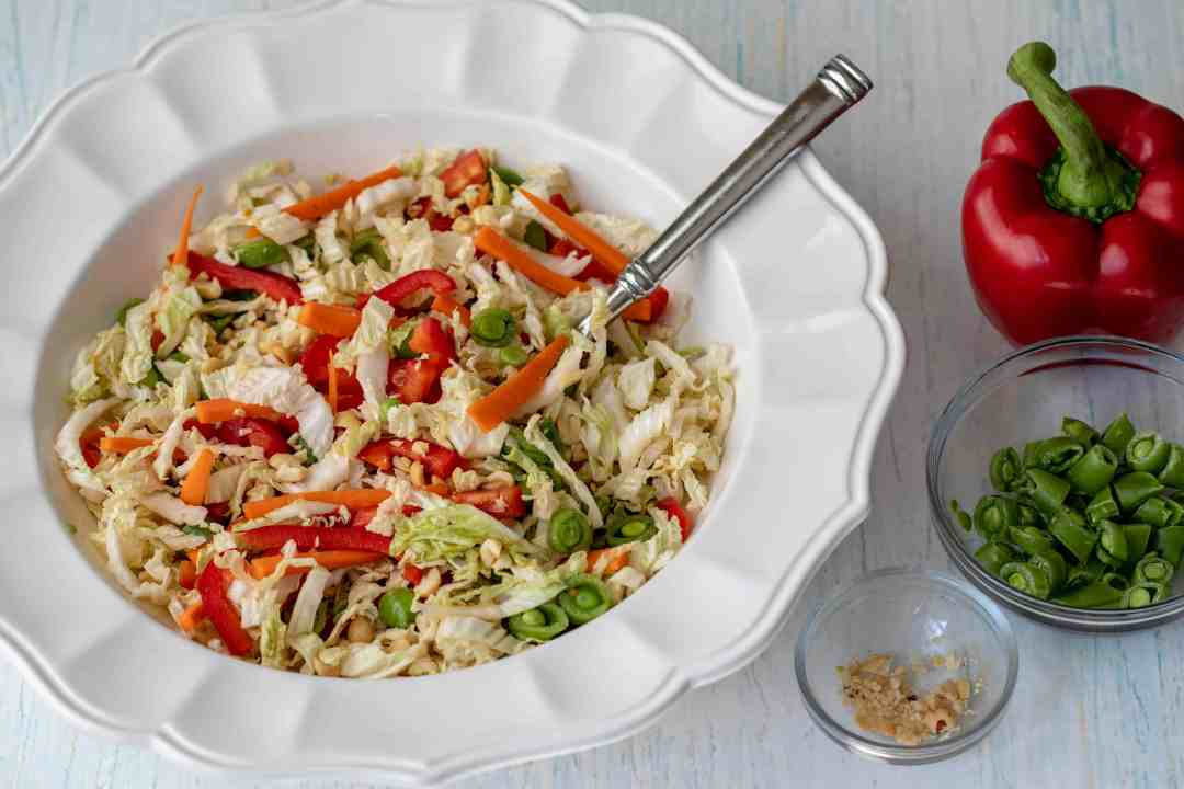 serving bowl of asian cabbage slaw next to bowls of peanuts and snap peas and a red bell pepper.
