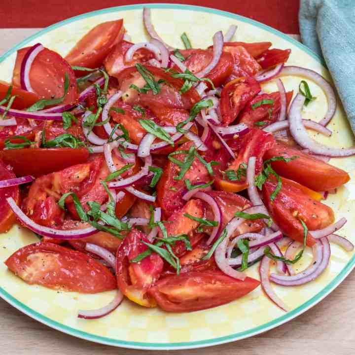 tomato salad with red onions and basil on a plate with green napkin