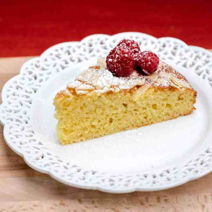 slice of French yogurt cake on white plate with raspberries on top