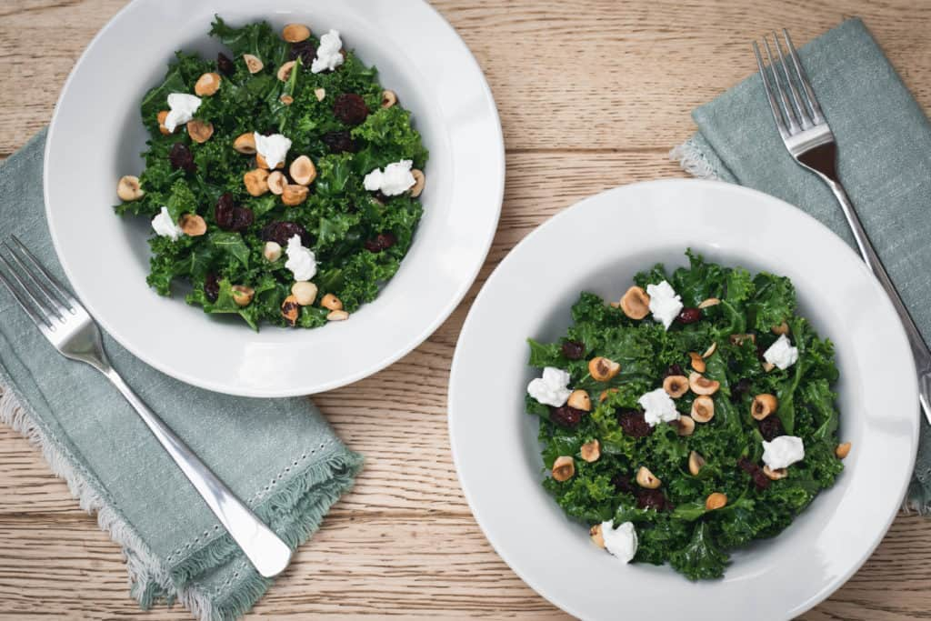 two bowls of kale salad with cranberries, plus napkins and forks