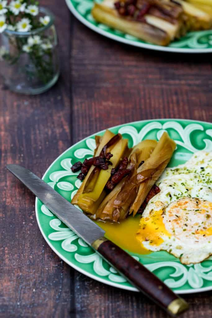 braised leeks with runny egg on plate with knife and flowers in background