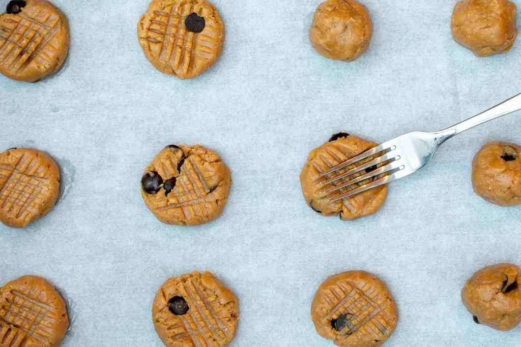 almond flour peanut butter cookies on sheet pan with cross-hatching