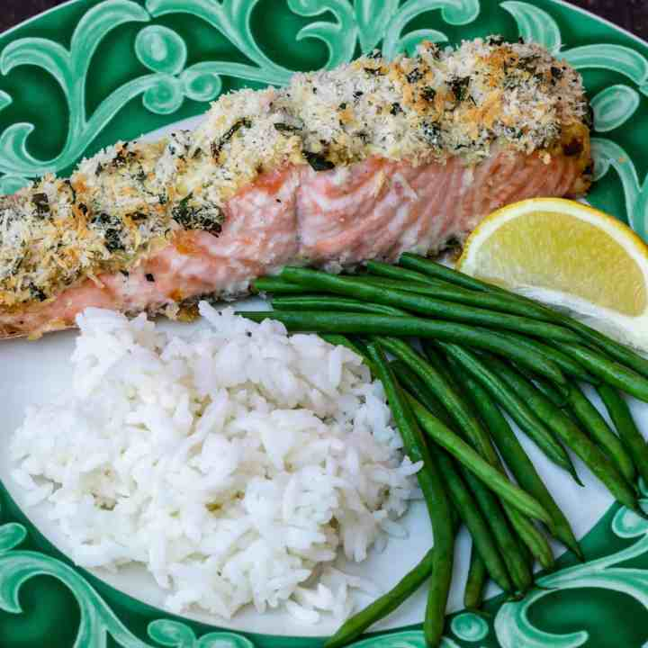 panko crusted salmon fillet with rice and green beans and lemon wedge on green plate