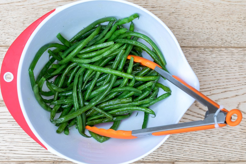 bowl of green beans tossed with olive oil, salt, and pepper