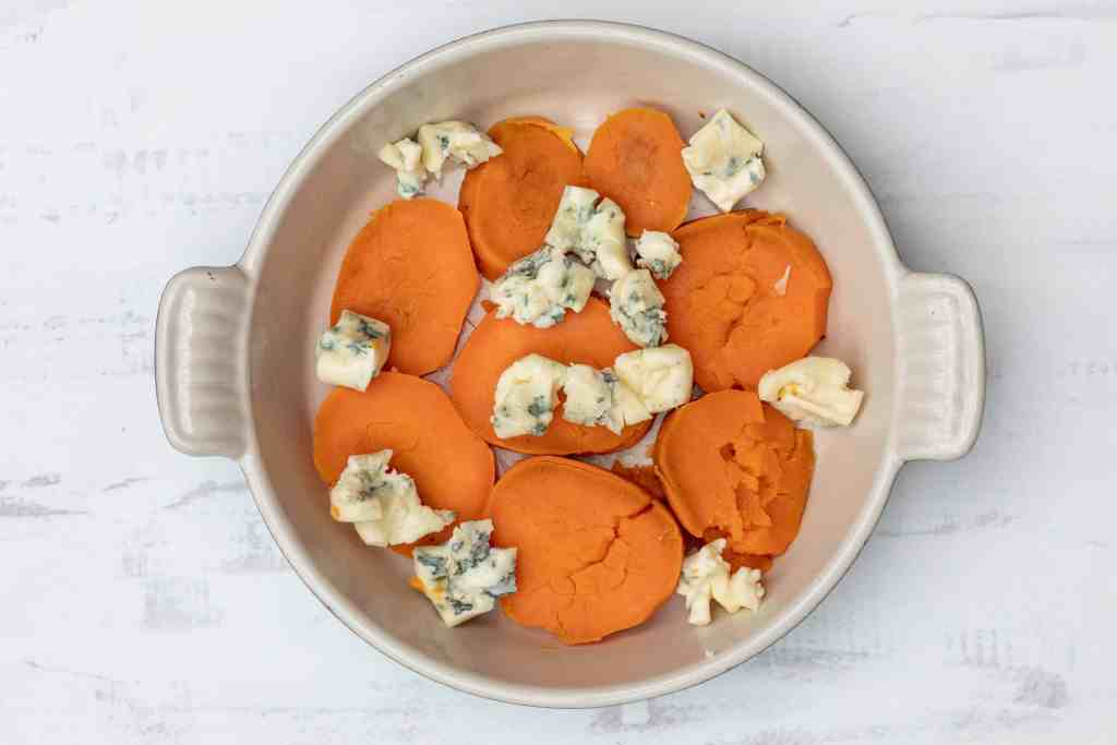 layer of sweet potato with blue cheese in gratin dish