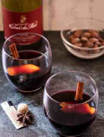two glasses of vin chaud with wine bottle and nuts in background