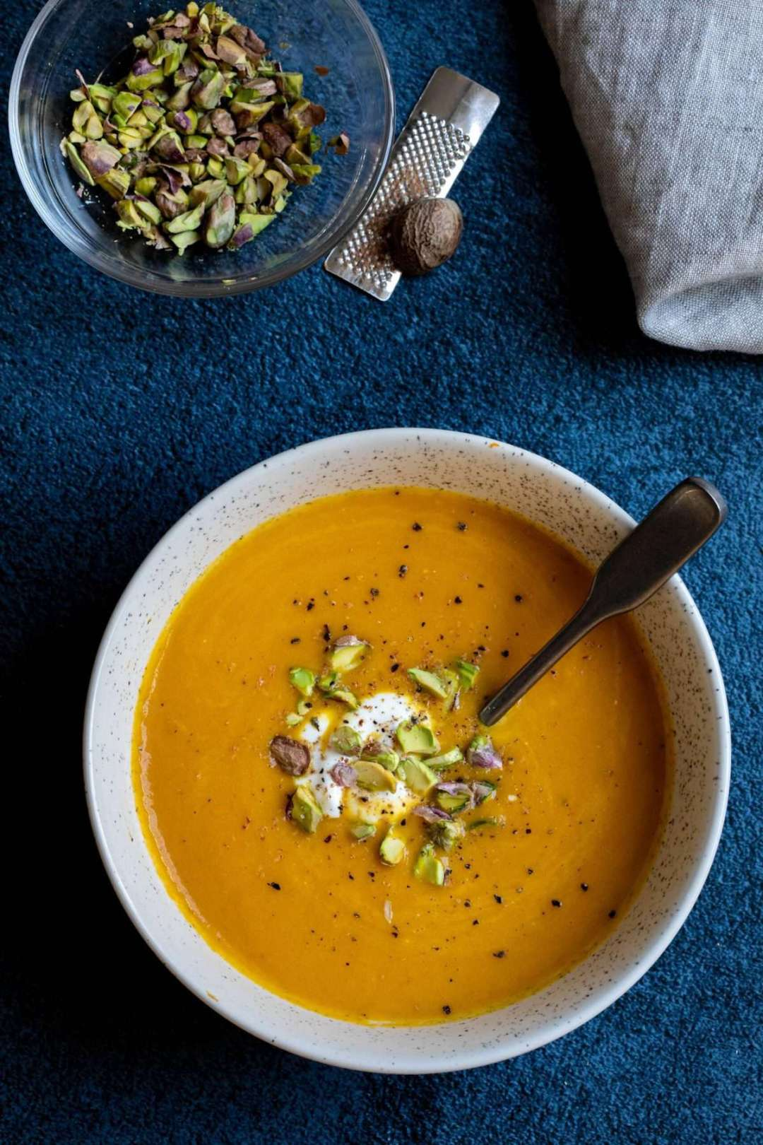 carrot ginger soup with small bowl of pistachios, nutmeg, and napkin