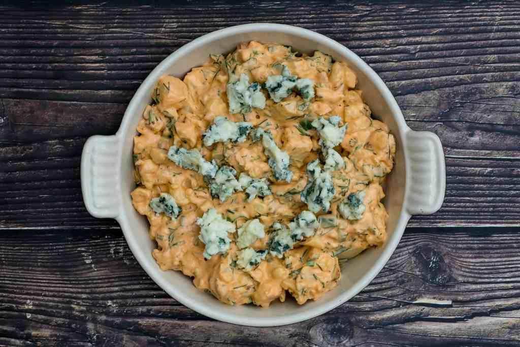 buffalo cauliflower dip in baking dish, ready for oven