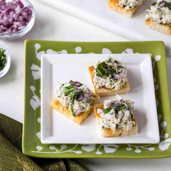 Cilantro-lime crab salad on paprika toasts on plates with toppings
