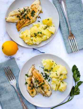sole meunière on small plates with napkins and forks and lemon