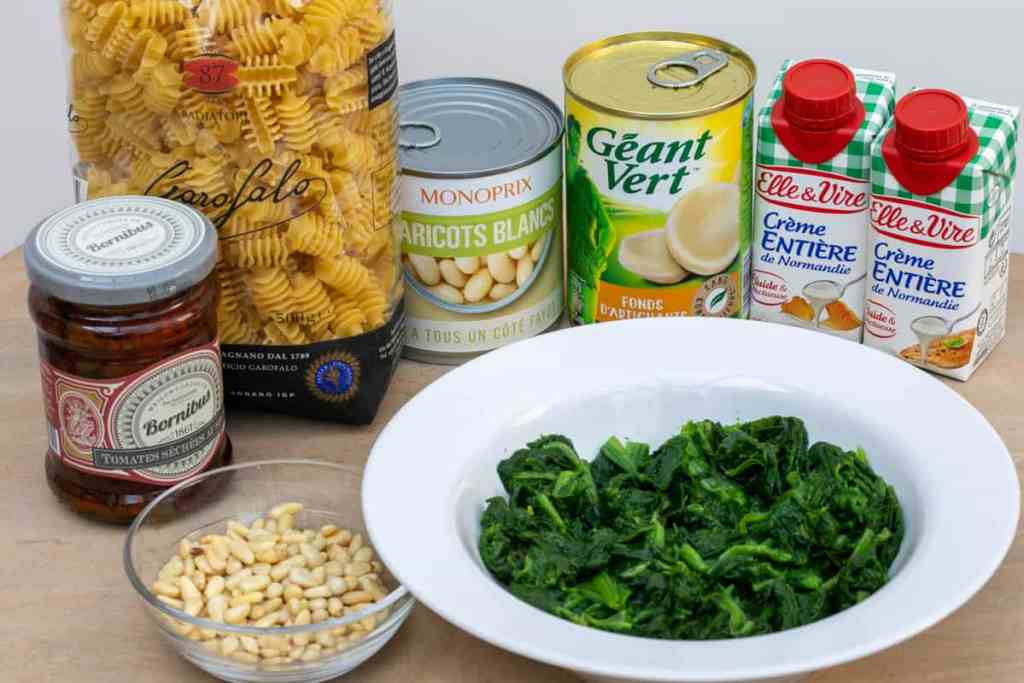 sun-dried tomatoes, pine nuts, pasta, white beans, artichoke bottoms, heavy cream, spinach