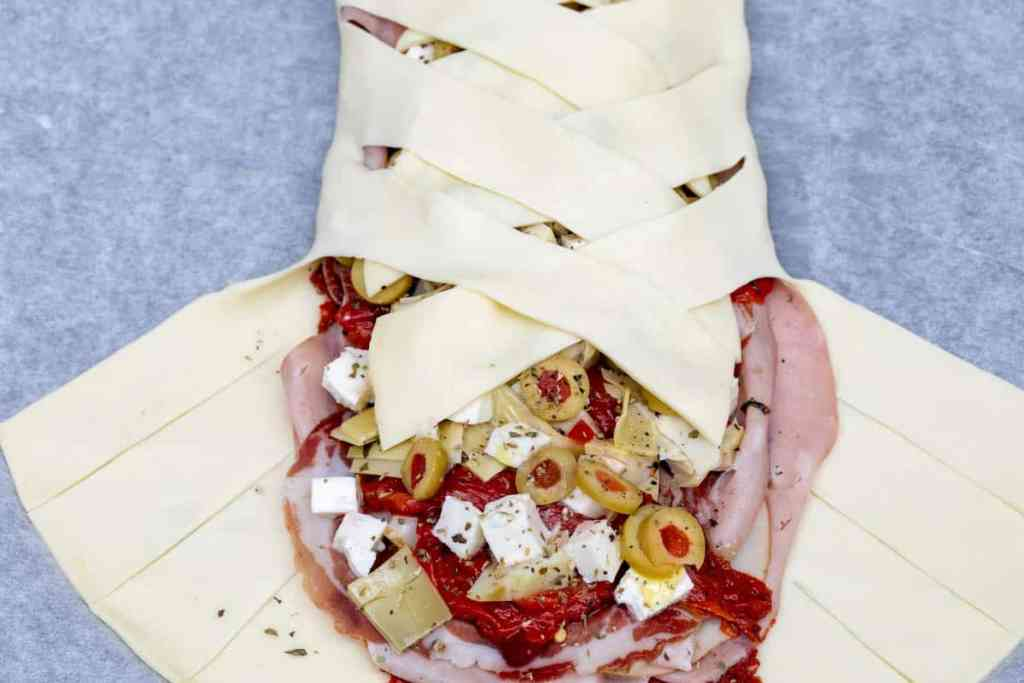 folding lattice of dough over filling for Antipasto Stromboli