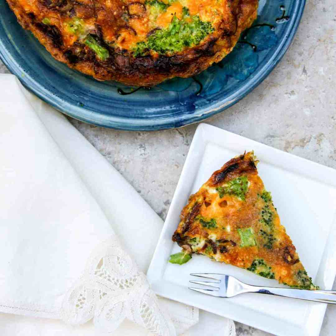 bacon, broccoli, and cheddar frittata slice on small plate with whole frittata in background