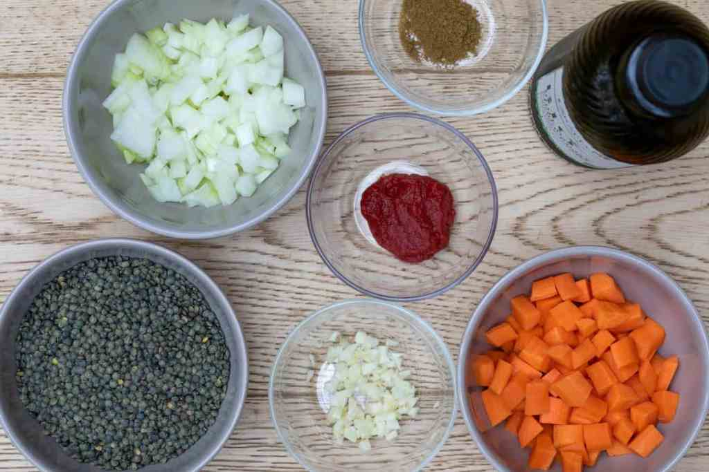 ingredients for french lentil soup: lentils, garlic, tomato paste, cumin, onions, carrots, olive oil