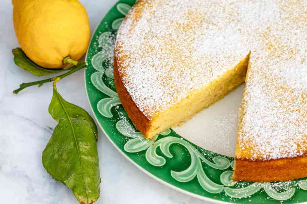 lemon ricotta cake on plate with lemon next to it