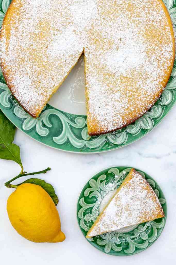 overhead shot of lemon ricotta cake with large cake and small plate with small slice, plus lemon
