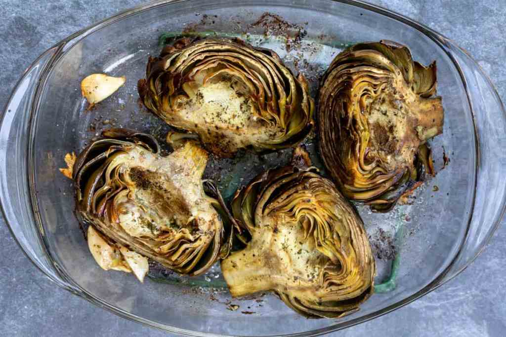 four roasted artichokes in baking dish with garlic cloves