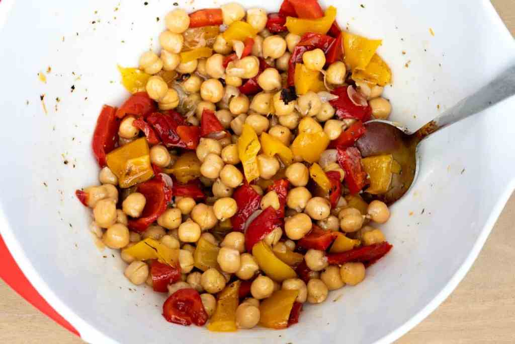chickpeas and roasted peppers tossed with red wine vinaigrette in large bowl with spoon
