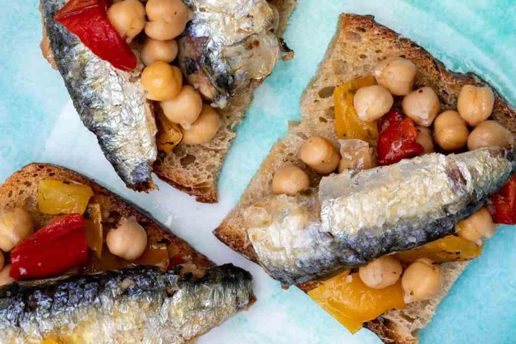 sardines on toast with chickpea salad close up on blue plate