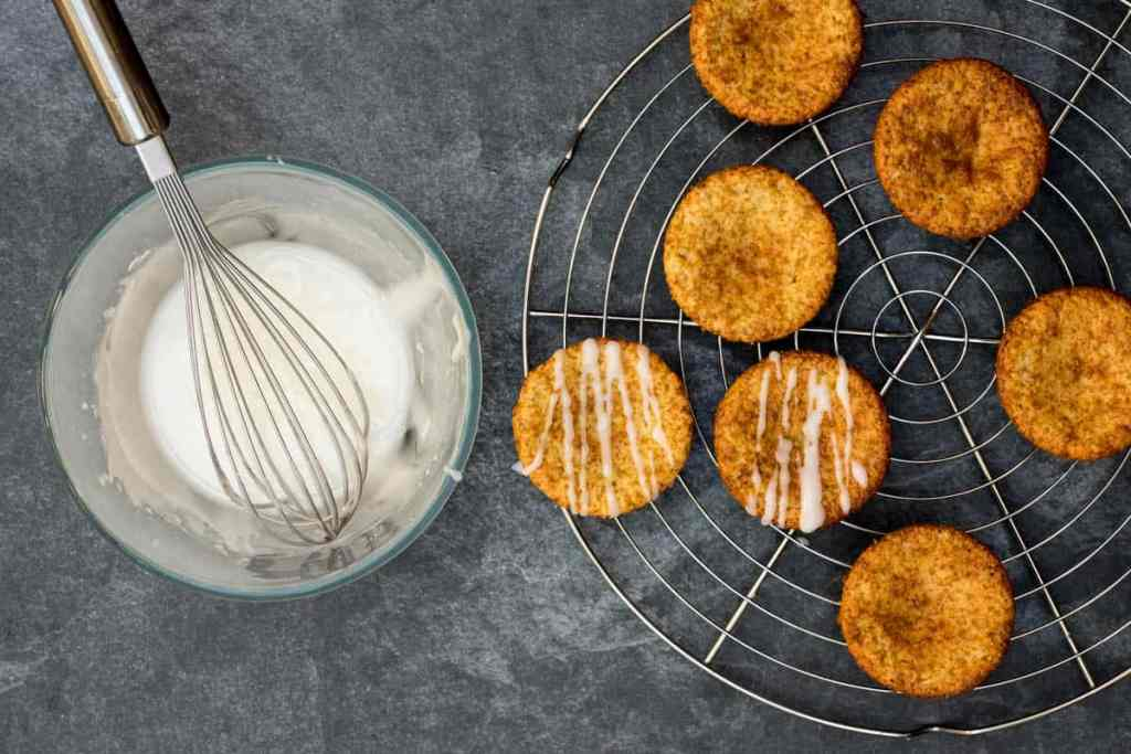 almond flour muffins on cooling rack with bowl of lemon glaze and whisk