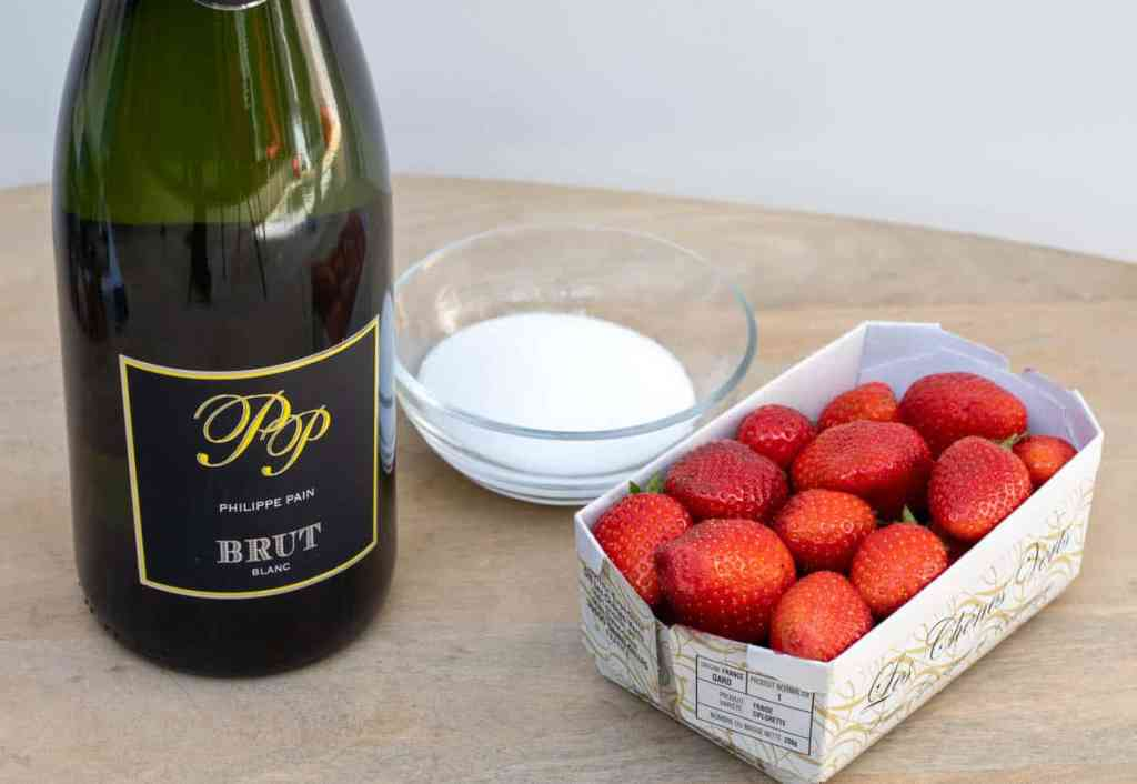 bottle of champagne, bowl of sugar, basket of strawberries