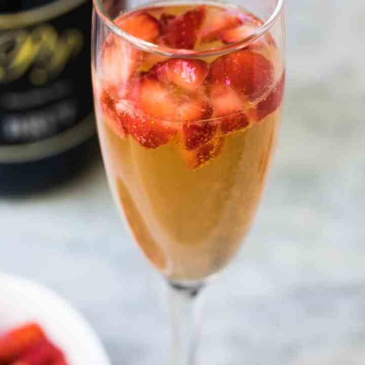 close up of glass of strawberry mimosa with bowl of chopped strawberries and champagne bottle in background
