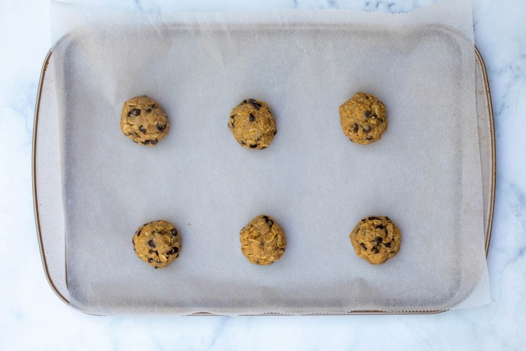 six almond flour oatmeal cookie balls on parchment-lined sheet pan