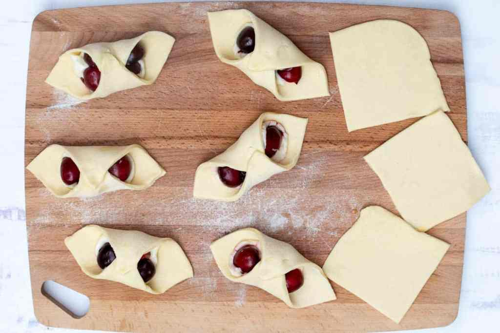puff pastry dough squares on cutting board, some folded into danishes and filled with cream cheese and cherries