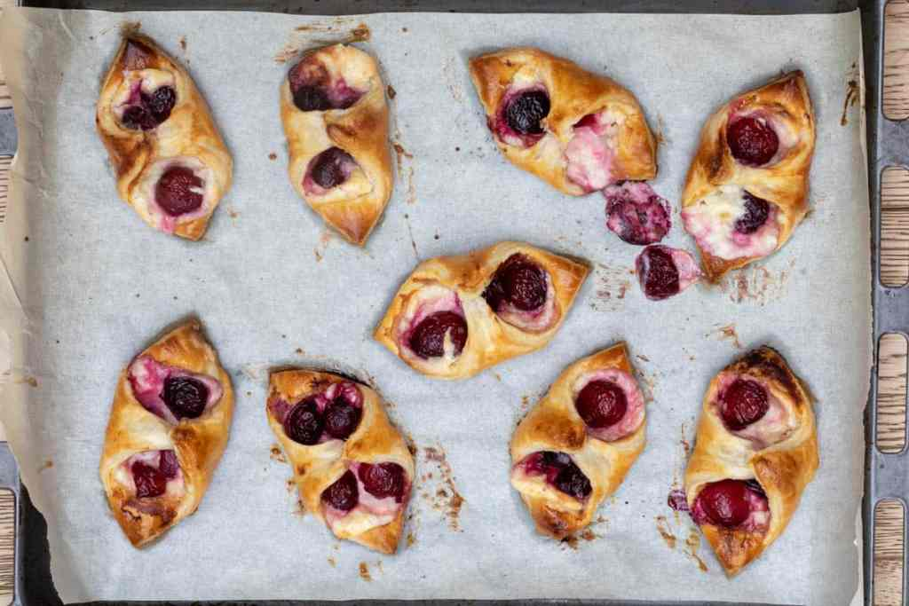 baked cherry cheese danishes with puff pastry on sheet pan