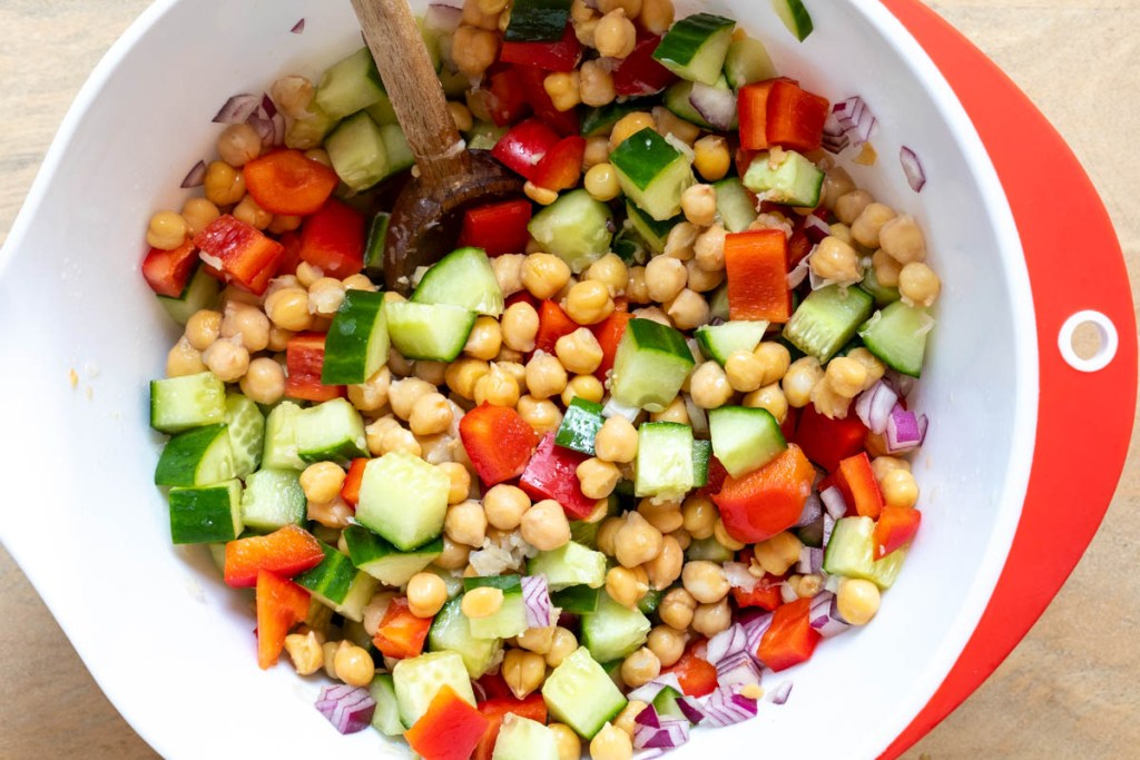 large bowl with chopped cucumbers, red pepper, chickpeas, and red onion
