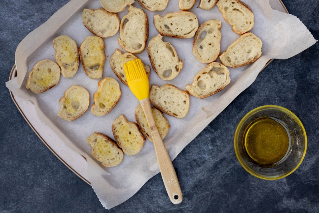 baguette slices on parchment-lined sheet pan with small bowl of olive oil and pastry brush