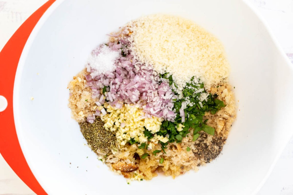 bowl with breadcrumbs, chopped garlic and shallots, parmesan cheese, and herbs and spices