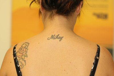 Black name neck tattoo before laser tattoo removal