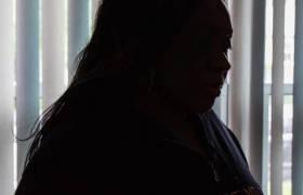 Violated traveler Tameika Lovell sitting in the dark [Photo Credit: The New York Daily News]