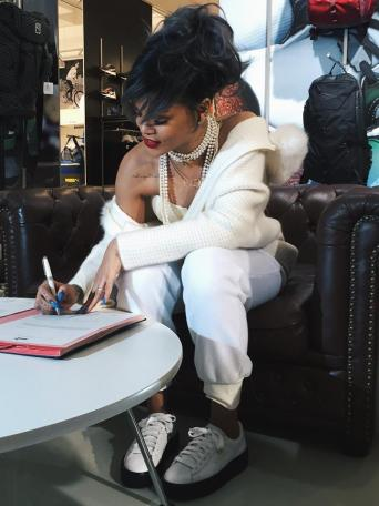 Rihanna signing the contract