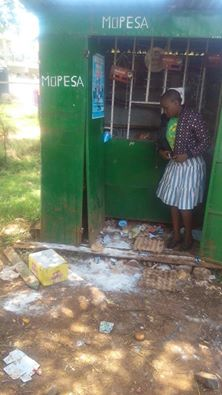 A nearby shopkeeper looks at the mess caused outside her Mpesa shop by the students