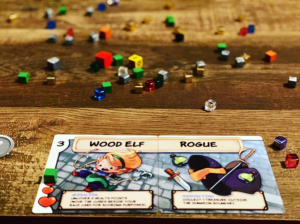 Race and Class card read Wood Elf and Rogue with cubes scattered in the background