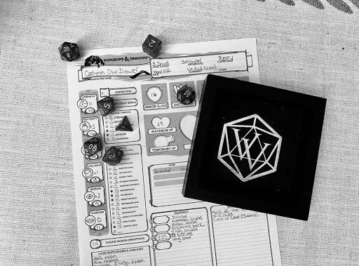 black and white image of a dungeons and dragons character sheet with a dice tray and set of polyhedral dice