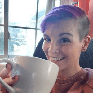 Smiling woman with purple hair and an undercut looks at the camera while drink coffee