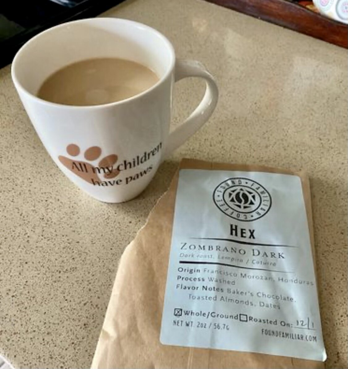 coffee cup next to a sample size bag of Hex