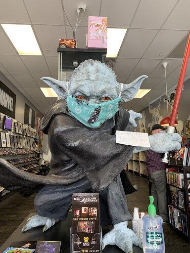 Grey Skinned Yoda, welding a red lightsaber, wears a mask