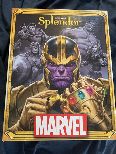 Splendor Marvel. It has a large full colored angry looking Thanos with the Marvel logo located at the bottom in white & red color. There are four Marvel heroes in black & white in the background. They include Dr. Strange, Captain America, Hulk,& Black Widow