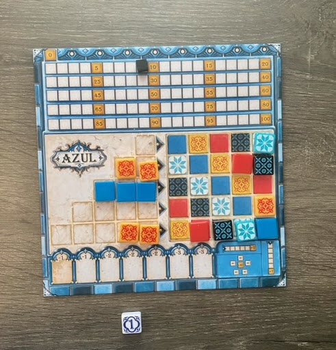 Pictured: a colorful Azul player card, with some tiles placed atop the card and filled in.