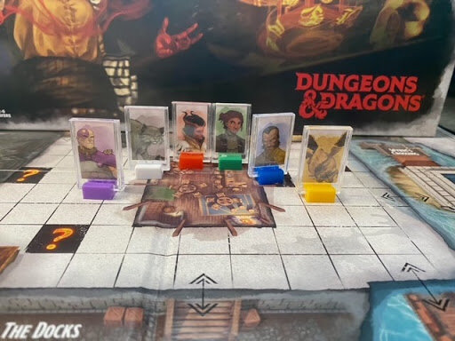 Pictured: 6 Meeples on the game board in front of the game box.
