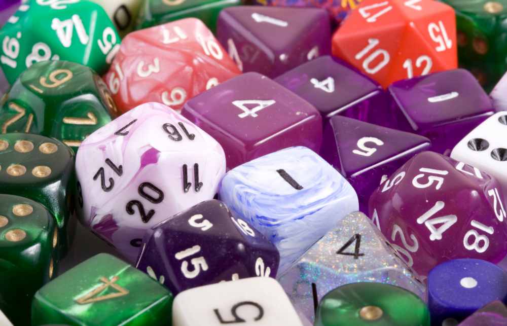 Pictured: Several polyhedral dice of various shapes in deep shades of purple, blue and green.
