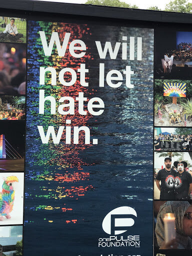 """Photo Description: The Phrase """"We will not let hate win."""" over water reflecting the colors of the rainbow. Photo credit: Allison J. Walker, taken at the interim Pulse Memorial in Orlando, FL"""