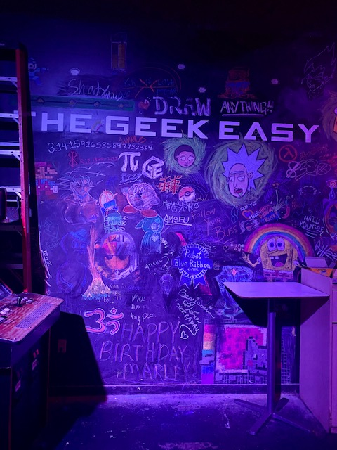 Pictured: Chalkboard reads The Geek Easy with many cartoon drawings surrounding the words