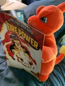 Stuffed Charmander reading a Free Power comic book